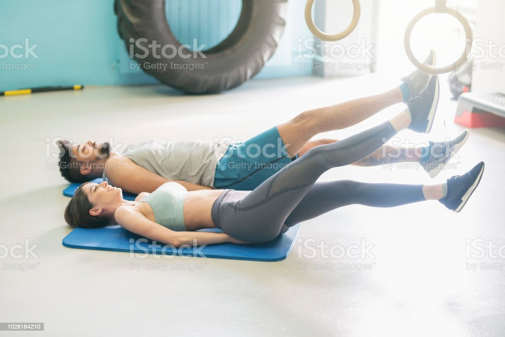 Young heterosexual couple doing a core workout at the gym.