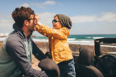 Photo of a little boy and his father on a road trip by the seaside in their convertible car, putting sunglasses on