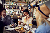 Close up of a group of friends enjoying food at a restaurant and using a mobile phone
