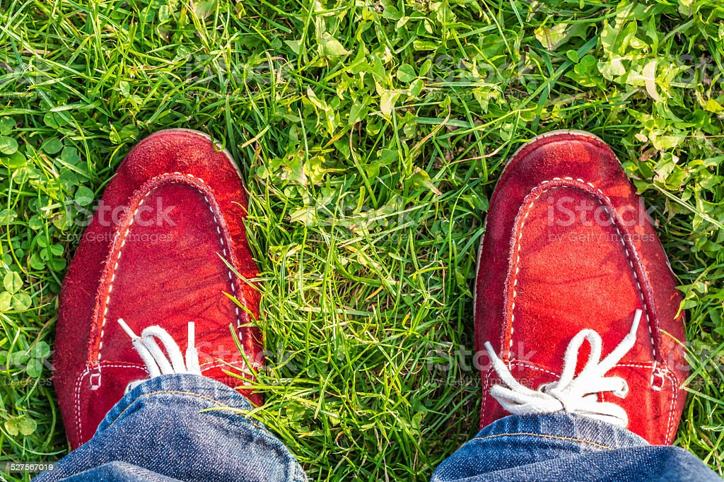 enjoying free day outdoors wearing red shoes, standing on green stock photo