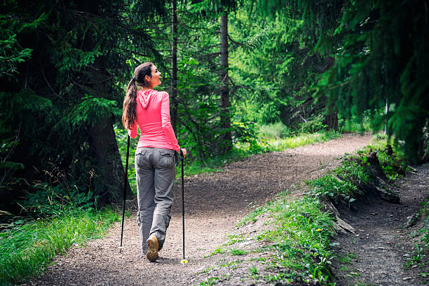 Enjoying Freedom in the Nature While the rest of the world is busy, a woman is enjoying the silence in the forest. Shot in Valais, Switzerland. nordic walking stock pictures, royalty-free photos & images
