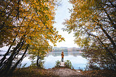 Idyllic autumn scene with woman standing on the wooden jetty by the lake.