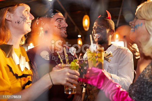Multi-ethnic group of friends wearing Halloween costumes drinking cocktails while enjoying party in club and having fun