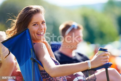 Portrait of an attractive young woman having a beer while sitting with her friends at a campsite