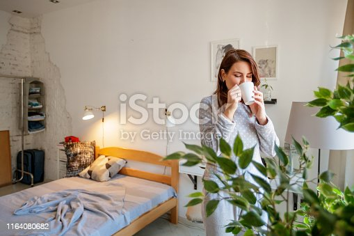 Mid adult woman enjoying her cup of morning coffee in pajamas in the bedroom