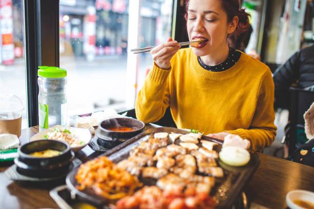 韓国レストランで彼女の旅行を楽しむ, バーベキューを試飲 - 韓国文化 ストックフォトと画像