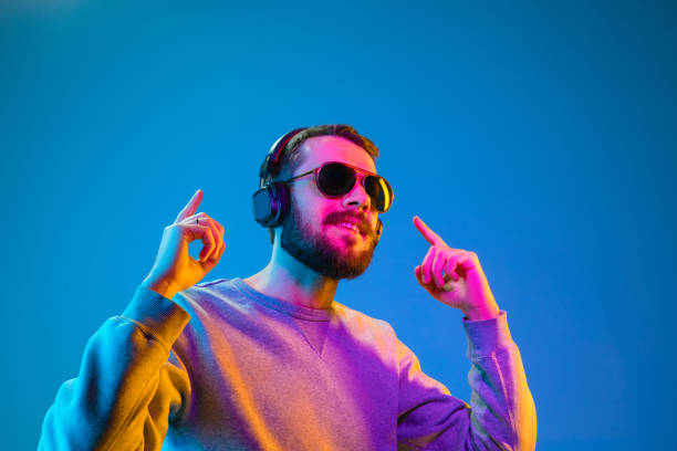 Enjoying his favorite music. Enjoying his favorite music. Happy young stylish man in hat and sunglasses with headphones listening and smiling while standing against blue neon background electronic music stock pictures, royalty-free photos & images