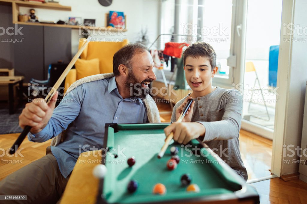 Photo of boy with his father playing pool at home