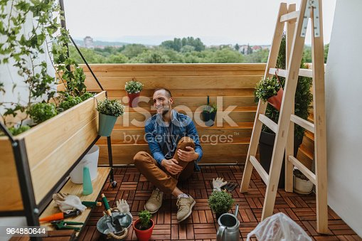 Photo of young gardener in a small garden on the balcony