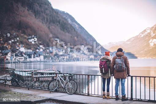 Young couple at winter mountain village. Standing on bridge and looking at the Hallstatt lake. Enjoying in nature. Wearing warm clothes, backpack. Winter day.