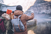 Young couple at winter mountain village. Standing on bridge and looking in the Hallstatt. Taking picture of beautiful view. Enjoying in nature. Wearing warm clothes, backpack. Winter day.