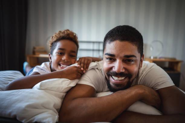 appréciant la grasse matinée avec papa - père célibataire photos et images de collection