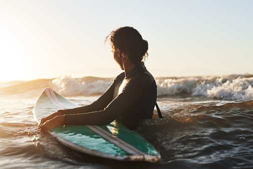 Shot of a beautiful young woman surfing in the ocean