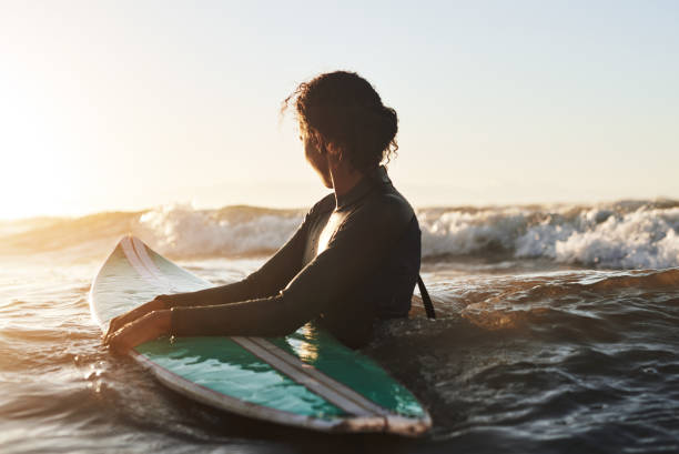 Enjoying life one wave at a time Shot of a beautiful young woman surfing in the ocean wetsuit stock pictures, royalty-free photos & images