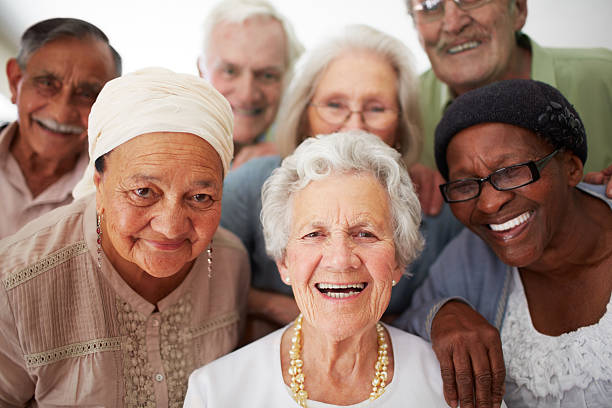 Enjoying life to the fullest everyday A group of seniors smiling together while in a retirement home aging stock pictures, royalty-free photos & images