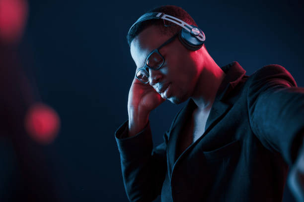 Enjoying listening music in headphones. In glasses. Futuristic neon lighting. Young african american man in the studio stock photo
