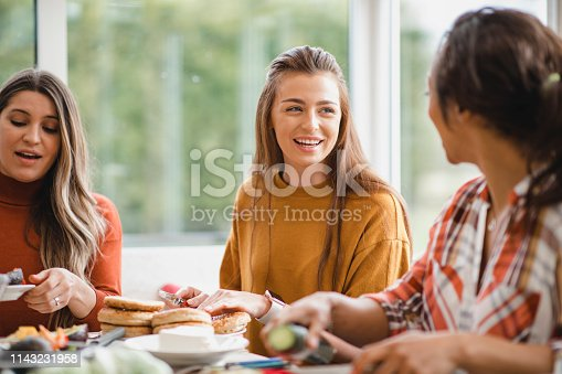 young female adult talking to her friend while having a healthy lunch. They are sitting inside of a conservatory, enjoying themselves.