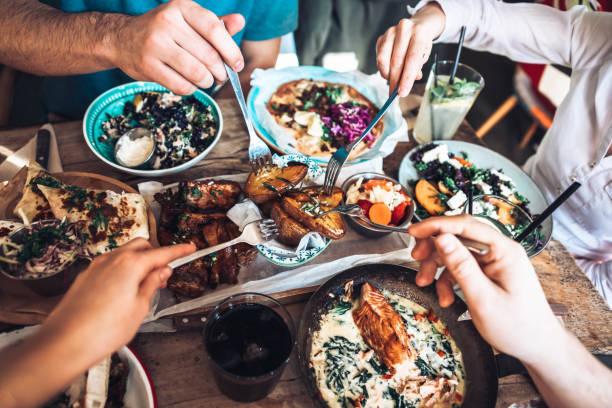 disfrutando el almuerzo con amigos - restaurante fotografías e imágenes de stock