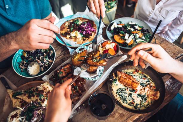 disfrutando del almuerzo con amigos - restaurante fotografías e imágenes de stock