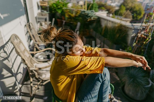 Photo of a woman sitting in a balcony, enjoying alone time and sunbathing