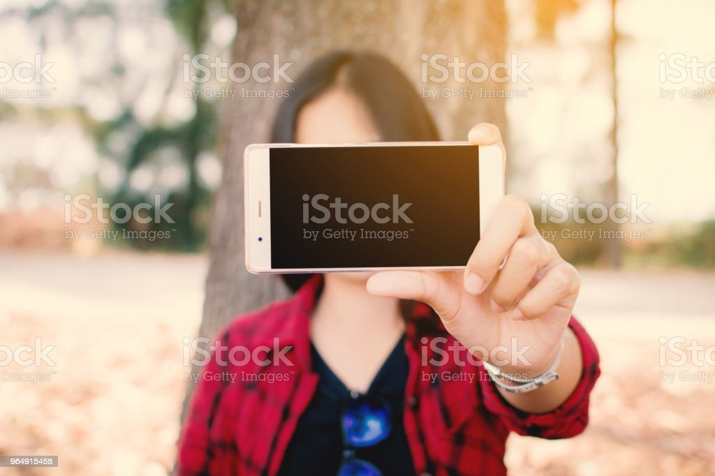 Enjoying moment woman using smartphone sitting under the big tree on park ,Relax time on holiday concept ,color of vintage royalty-free stock photo