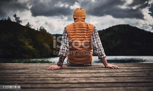 Tourist Enjoying moments of silence  sitting on the pier in the mountains