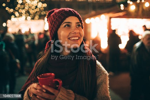 Young woman drinking mulled wine at Christmas market