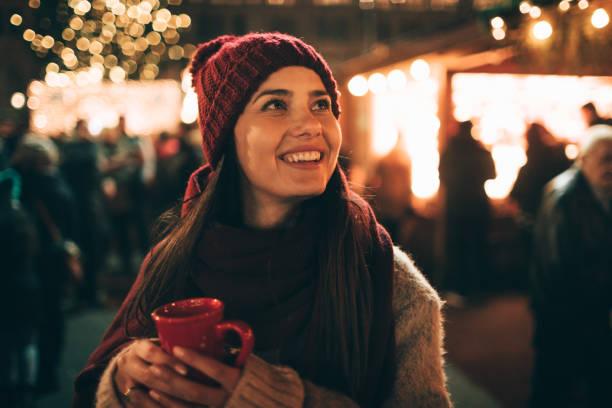 genieten van glühwein op kerstmarkt - gluhwein stockfoto's en -beelden