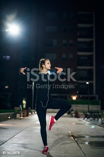 Young female athlete exercising in park at night