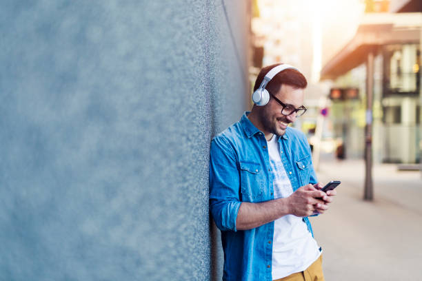 Enjoying music Smiling young attractive man listening music on the street headphones stock pictures, royalty-free photos & images