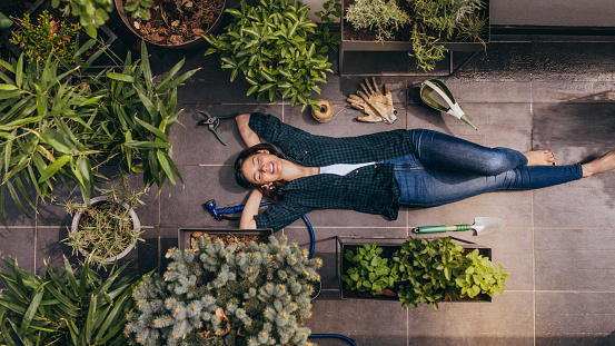 Young woman lying in her rooftop garden, taking a break from gardening