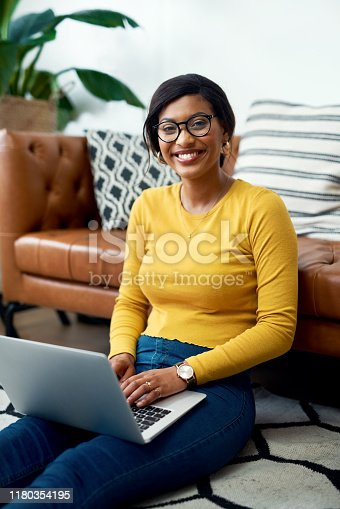 Cropped shot of an attractive young woman sitting on the floor and using her laptop at home