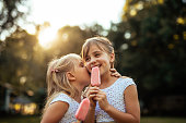 Shot of a two young girls whispering while eating ice cream outdoors at sunset.