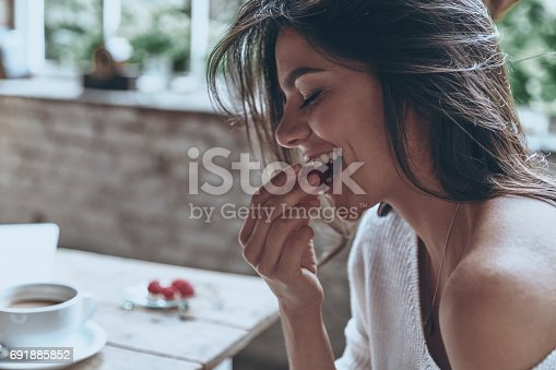 Attractive young woman keeping eyes closed and eating raspberries while having breakfast at home