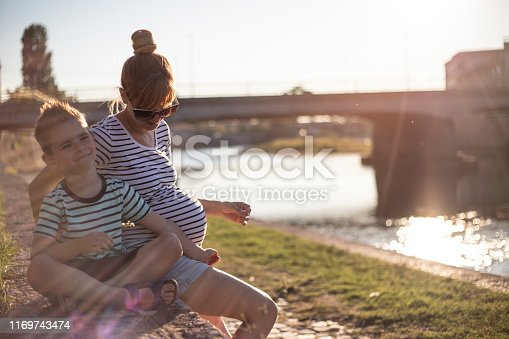 Young pregnant woman sitting by the river and enjoying with her five years old son.