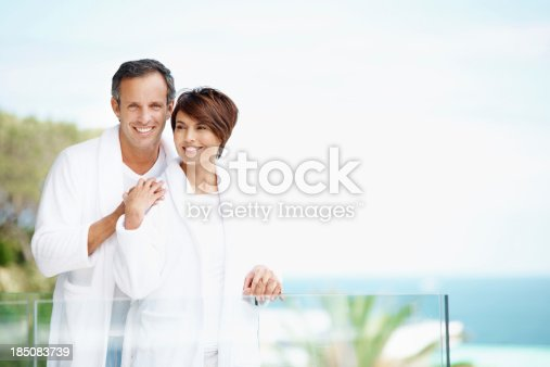 A happy couple on a balcony wearing white bathrobes