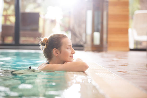 Enjoying peace and quiet Side view of a Caucasian woman resting at poolside. She is enjoying a quiet weekend at the spa. spa stock pictures, royalty-free photos & images