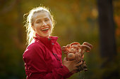 lifestyle shot of smiling blond hair woman in the forest picking mushroomes and enjoying it.