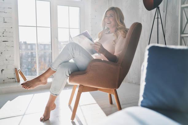 genieten van de lezing. - woman home magazine stockfoto's en -beelden