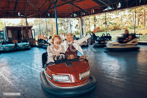 playful senior couple having fun together driving bumper car
