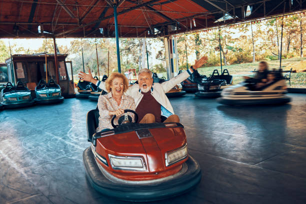 enjoying retirement playful senior couple having fun together driving bumper car leisure equipment stock pictures, royalty-free photos & images