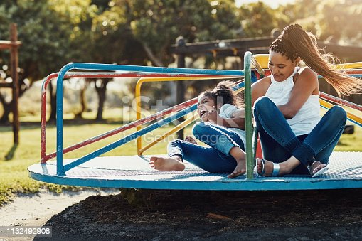Full length shot of a mother and her daughter playing together on a merry-go-round at the park