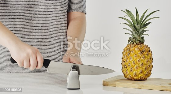 Cropped shot of an unrecognizable woman sharpening a knife before cutting into a pineapple in the kitchen
