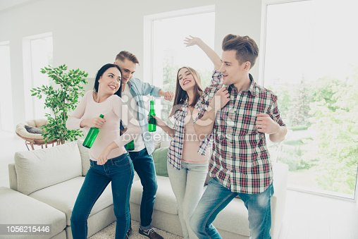 istock Enjoying spending time together! Careless, funkey, positive mood, stylish, attractive, handsome guys, beautiful girls having party with dancing singing holding bottles with lager 1056215446