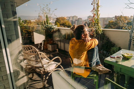 Photo of a woman drinking first morning coffee, eating 'take out' food and reading daily news online - on the balcony of her apartment while enjoying springtime sun