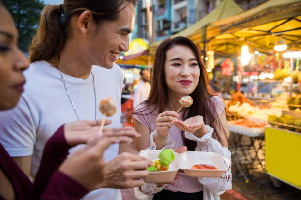 Enjoying street food at a local night market Friends eating local cuisine at a night market night market stock pictures, royalty-free photos & images