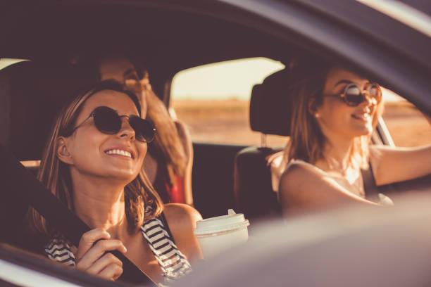 Genießen Sie sommerliche Sonne während der Fahrt im Auto mit Freunden – Foto