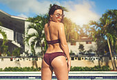 Rearview shot of a beautiful young woman at the swimming pool outside