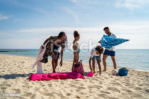 Parents and their children are settling down on the sandy beach.