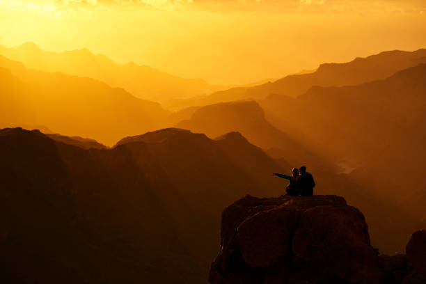 enjoying sunset together - mountain sunset stock photos and pictures